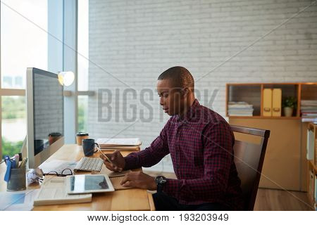 Profile view of concentrated manager wearing checked shirt texting with colleague on smartphone while sitting at desk in modern office with panoramic windows