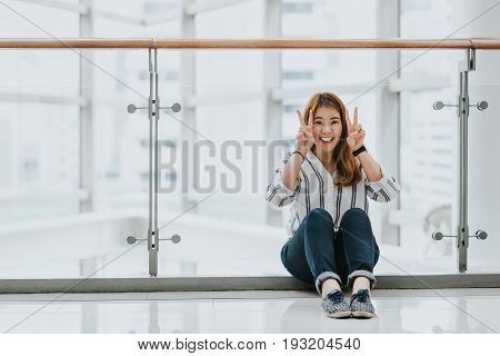 Young happy Asian girls laugh and smile while doing victory sign both hand indoor.