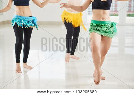 Unrecognizable female belly dancers shaking their hips in spacious dance hall with panoramic windows