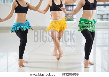 Group of young women gathered together in spacious dance hall and performing belly dance movement