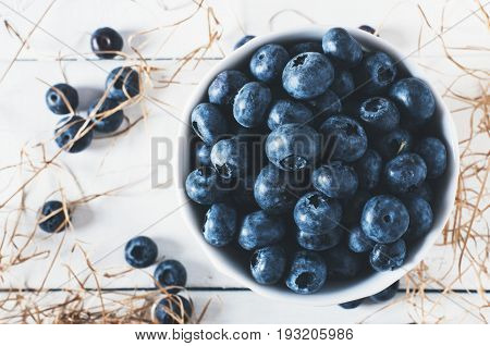 Blueberries on vintage wooden white background top view healthy food on dark table mockup berry for smoothie with vintage metal spoon isolated on rustic country board fresh bilberry mock up closeup