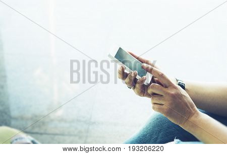 Young hipster girl sitting at airport with yellow suitcase traveling in Europe female hands using making smartphone in terminal area hall tourist journey trip concept mockup blank screen sellphone