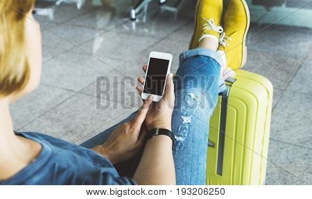 Young hipster girl sitting at airport and put feet in yellow boot on suitcase traveling female hands using app on making smartphone in terminal area hall tourist journey trip concept mockup blank screen