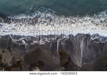 Aerial image of a beach with incoming wave
