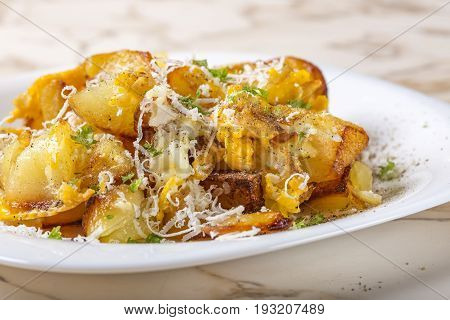 Fried potatoes with scrambled eggs and parmesan cheese on white plate