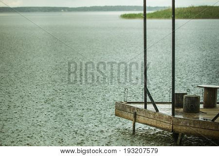 Lonely fishing pier on a lake under heavy shower rain. Bad weather. Bad mood concept. Gloomy colors