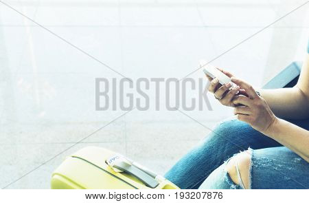 Young hipster girl sitting at airport in yellow boot on suitcase traveling in Europe female hands using app on making smartphone in terminal area hall tourist journey trip concept mockup blank screen sell phone