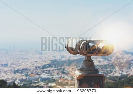 Touristic telescope look at the city with view of Barcelona Spain close up old metal binoculars on background viewpoint overlooking the mountain hipster coin operated in panorama observation mockup poster