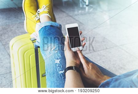 Young hipster girl at airport in yellow boot on suitcase waiting air flight female hands holding smart phone in terminal departure lounge gate traveler trip concept mockup of blank screen sellphone