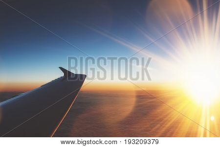 Clouds and sunlight as seen image through window an aircraft. Looking out the window of plane. Airplane in the blue sky at sunrise. View wing from the inside on background sunset mockup