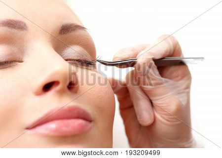 Eyelash styling. The beautician prolongs and thickens eyelashes.