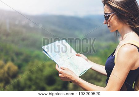 Hipster young girl with bright backpack enjoying panoramic mountain sea using map and looking distance. Tourist traveler on background landscape Barcelona view mockup sun flare in trip holiday