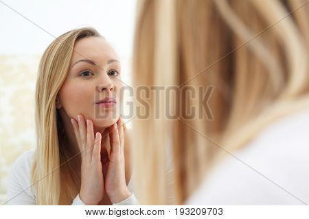 Skin care. The woman looks in the mirror and checks the condition of the skin