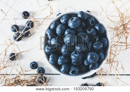 Blueberries on vintage wooden white background top view healthy food on dark table mockup berry for smoothie with vintage metal spoon isolated on rustic country board fresh bilberry mock up closeup copy space for text design