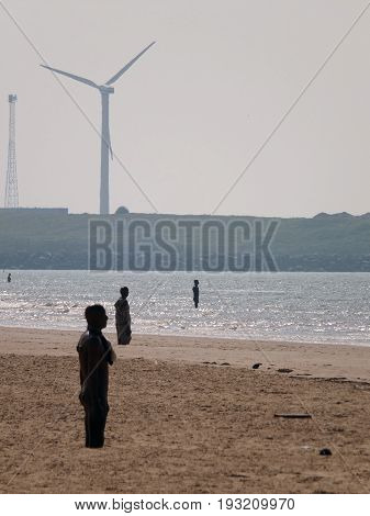 windmills and statues by anthony gomley on crosby beach in mersyside