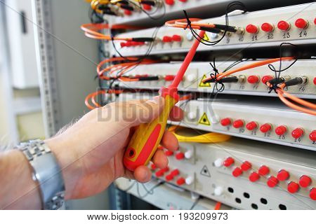 Repair of industrial optical commutator. Optical fibre information technology equipment in data center. Fiber optical switch with connected FC cables in server room