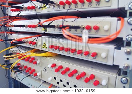 Fiber optical switch with connected FC cables in server room. Communication equipment opto cable. Optical fibre information technology equipment in data center