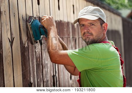 Man removing old cracked paint from a fence using an electic vibrating sander - working in sunshine