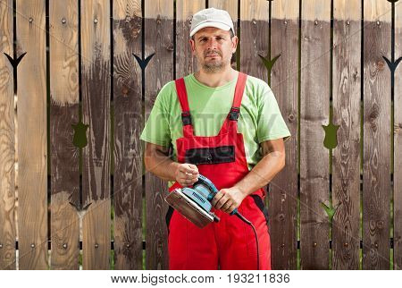 Worker man scraping old cracked paint from fence with an electric vibrating sander