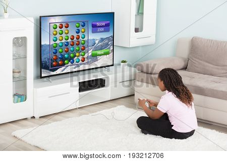Girl Sitting On White Carpet Plying Video Games At Home