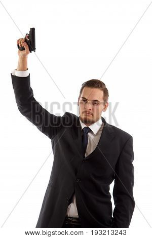 A man in a suit holding a gun in the air