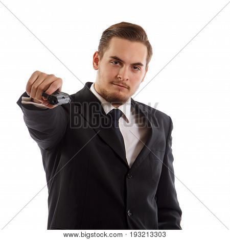 An armed man in a suit pointing a handgun