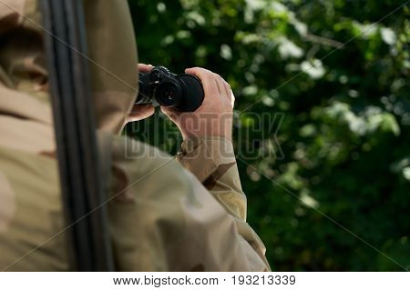 Man hunter in camouflage clothes with shotgun looking through binoculars in forest. Hunting and people concept.