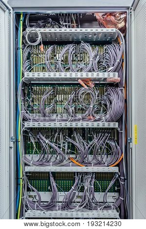 Inside the cabinet with telecommunication mobile network equipment with many cables