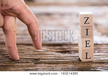 Close-up Of A Person's Finger And Stacked Ziel (Goal in German) Word From Wooden Blocks