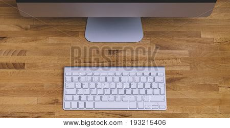 Top view of a computer monitor with a blank screen on a pure white background of a brick wall and a keyboard on a wooden table blank for your text or content or design closeup. Mock up top view