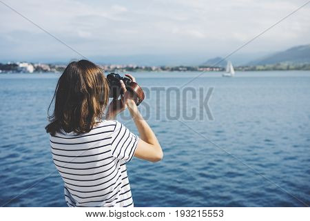 Hipster photograph on vintage camera or technology mock up. Girl using vintage camerae on blue sea and yacht background close. Blurred backdrop. Mockup front view. Copy space for text message or design