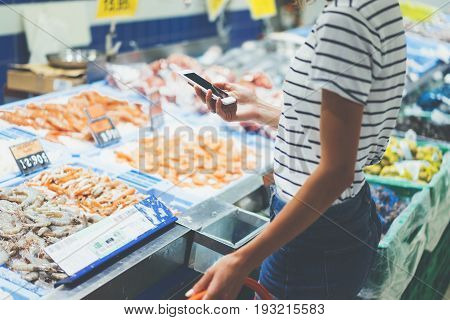 Young woman shopping healthy food in supermarket blur background. Close up view girl buy products using smartphone in store. Hipster at grocery using smartphone. Person comparing the price of produce of with her digital gadget at store.