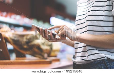 Young woman shopping healthy food in supermarket blur background. Close up view girl buy jamon using smartphone in store. Hipster at grocery using smartphone. Person comparing the price of produce of with her digital gadget at store.