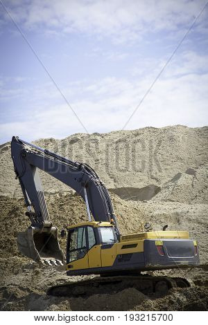 A large yellow excavator on the road construction site picks up and pours sand rubble stones in a quarry construction machinery excavator digs