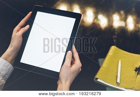 Closeup of a woman pointing finger to an blank display of the tablet with a blue color in a homelike atmosphere on warm bokeh background lighting color female hends using computer in cafe with reflection and glare poster