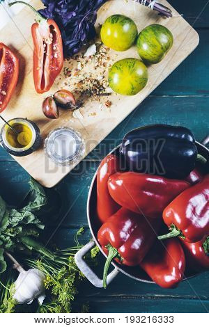 Red and black pepper in a metal bowl on wooden background and yellow tomatoes with basil and spices on a cutting board top view a healthy natural food closeup
