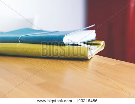 close-up of brightly colored notebooks on wooden table on red background side view of the object free space blurred and free space for your text or content or design