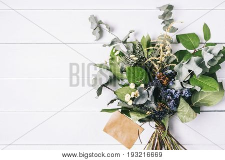 Bouquet of dried wild flowers on white table background with natural wood vintage planks wooden texture top view horizontal empty space for publicity information or advertising text