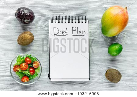 Heathy food for slimming. Notebook for diet plan, fruits and salad on grey wooden table top view mock up.