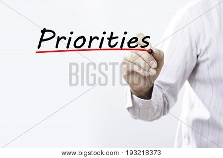 Businessman hand writing Priorities with marker Business concept