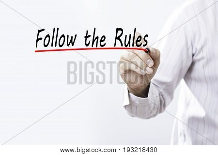 Businessman hand writing Follow the Rules with red marker on transparent wipe board business concept