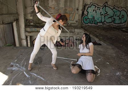 Two Business Women Are Fighting At Swords. One Of Them Is Defeated