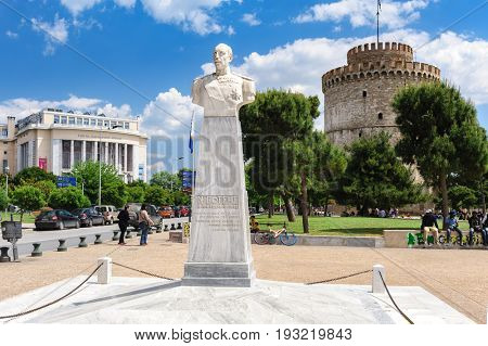 Thesalloniki, Macedonia, Greece - 12th May 2015: People walking and relaxing near white Tower behind admiral Votsis statue, Thessaloniki, Greece.