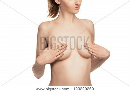 nude Female breast. Young caucasian adult woman examining her breast for lumps or signs of breast cancer.Isolated white background.