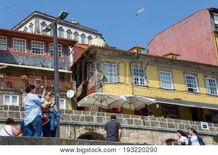 PORTO, PORTUGAL - APRIL 17, 2017: Tourists and locals enjoy the Ribeira in the Douro River bank near the Dom Luis I Bridge, Porto, Portugal.