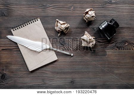 Writer concept. Feather pen, ink and crumpled paper on wooden table background top view copyspace.