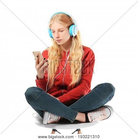Cute teenager girl with mobile phone and headphones listening to music on white background