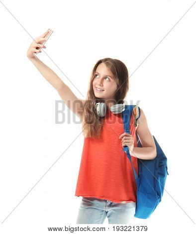 Cute teenager girl with headphones and schoolbag taking selfie on white background