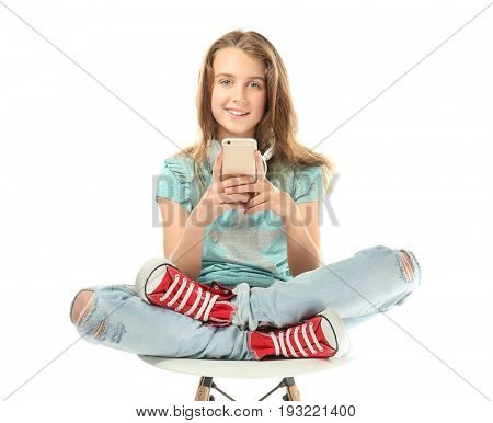 Cute teenager girl with mobile phone and headphones on white background
