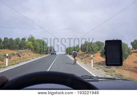 Driving slowly behind a cyclist by local road over solid line. View from the inside of the car